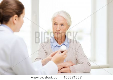 medicine, age, health care and people concept - doctor showing pills to senior woman at hospital