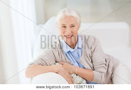 age and people concept - happy smiling senior woman sitting on sofa at home
