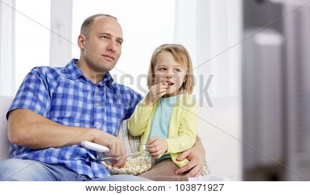 family, children, parenthood people concept - happy father and daughter eating popcorn and watching tv at home
