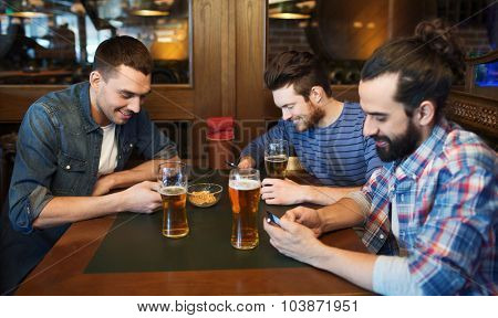 people, men, leisure, friendship and technology concept - male friends with smartphones drinking beer at bar or pub