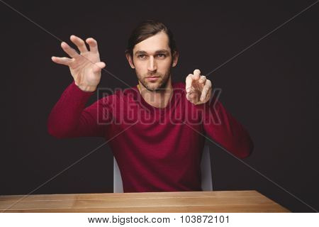Man gesturing while sitting at desk in office