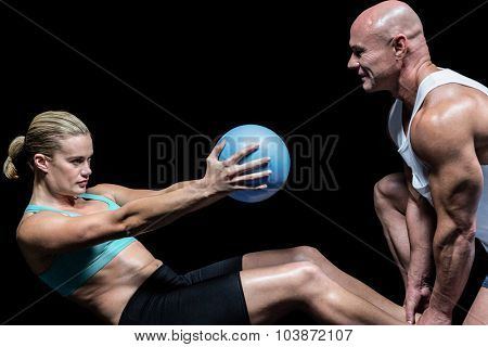 Trainer assisting woman doing crunching exercise against black background