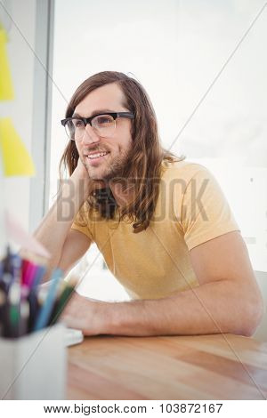 Happy hipster wearing eye glasses working at desk in office