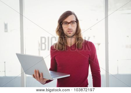 Portrait of hipster holding laptop against window in office