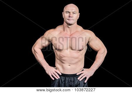 Portrait of bald man with hand on hip standing against black background