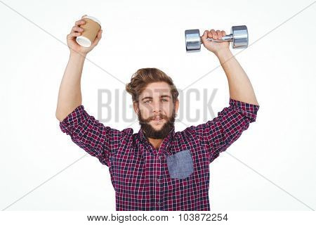 Portrait of hipster holding dumbbells and disposable cup against white background