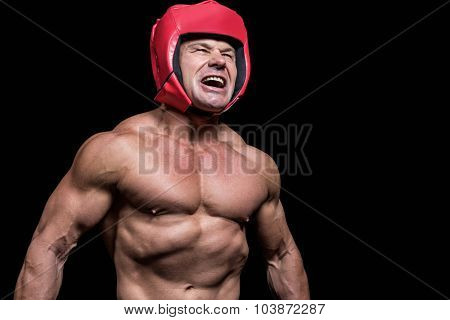Angry boxer with red headgear against black background