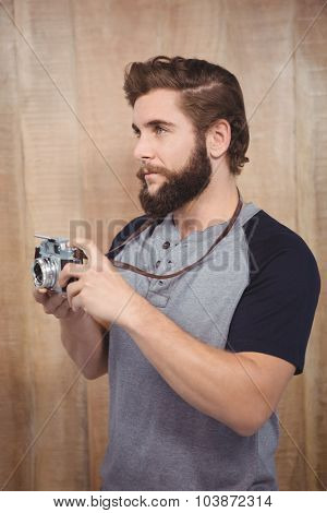 Hipster using digital camera against wooden wall