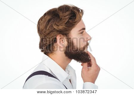 Profile view of hipster touching beard against white background