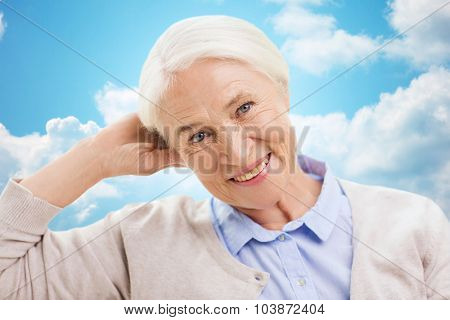 age and people concept - happy smiling senior woman over blue sky and clouds background