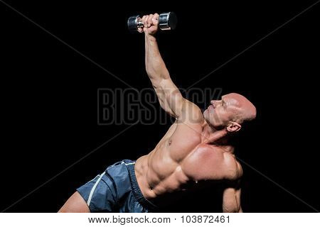 Man exercising with dumbbells against black background