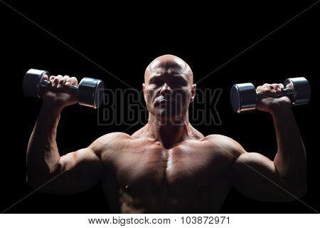 Portrait of man exercising with dumbbells against black background