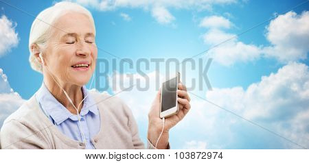 technology, age and people concept - happy senior woman with smartphone and earphones listening to music over blue sky and clouds background