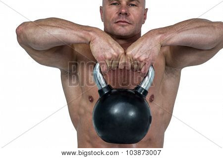 Close-up of kettlebell lifted by muscular man against white background
