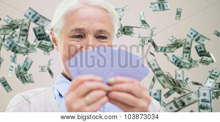 age, game, gamble, poker and people concept - close up of happy smiling senior woman playing cards over dollar money rain on background