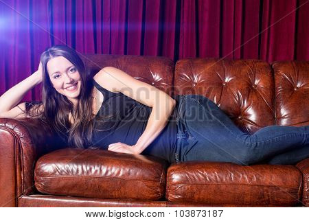 Young attractive woman sitting on a leather couch