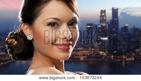 people, holidays, jewelry and luxury concept - smiling woman face with diamond earring over night singapore city background