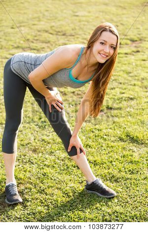 Young woman outside stretching after her workout