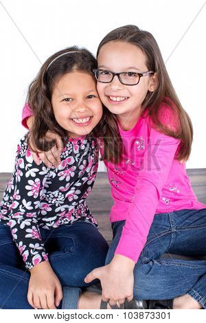 Two cute little girls sitting on the floor together