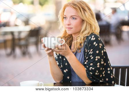 Woman having a coffee alone at a cafe