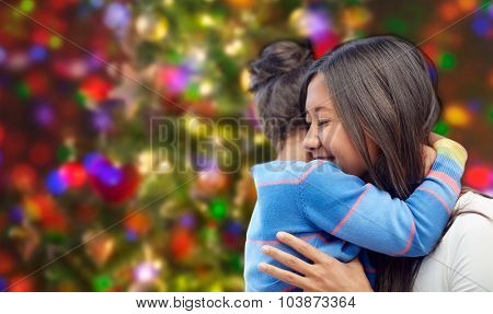 family, children, love and happy people concept - happy mother and daughter hugging over lights background