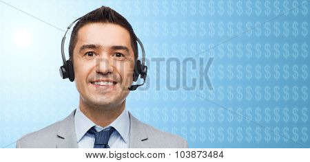 business, finances, people, technology and service concept - smiling businessman in headset over blue background with dollar currency symbols