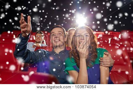 cinema, entertainment and people concept - happy couple watching movie in theater over snowflakes