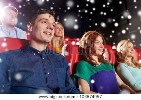 cinema, entertainment and people concept - happy friends watching movie in theater over snowflakes