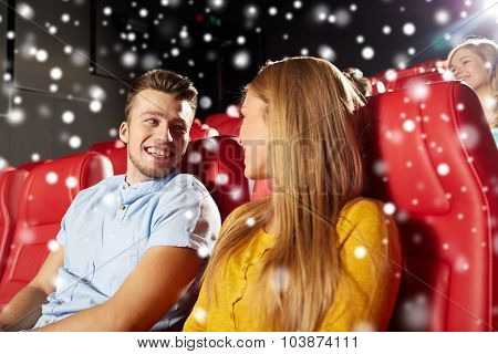 cinema, entertainment and people concept - happy friends or couple watching movie and talking in theater over snowflakes