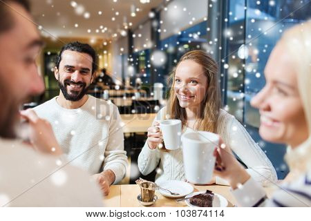 people, leisure, communication, season and concept - happy friends meeting and drinking tea or coffee at winter cafe
