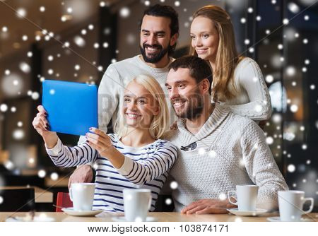 people, leisure, communication, technology and season - happy friends with tablet pc computer taking selfie at winter cafe