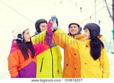 winter, leisure, extreme sport, friendship and people concept - happy friends in helmets making high five gesture