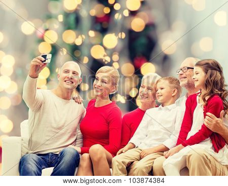 family, holidays, generation, christmas and people concept - smiling family with camera taking selfie and sitting on couch over tree lights background