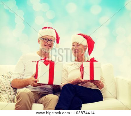 family, holidays, christmas, age and people concept - happy senior couple in santa helper hats with gift boxes over blue lights background