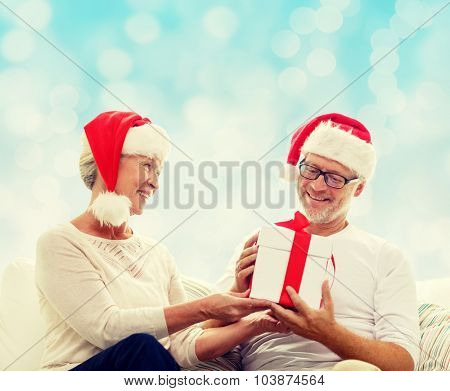 family, holidays, christmas, age and people concept - happy senior couple in santa helper hats with gift box over blue lights background