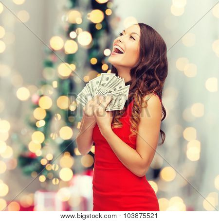 holidays, sale, banking and people concept - smiling woman in red dress with us dollar money over christmas tree lights background