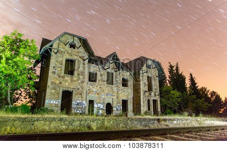 Abandoned train station with star trails at night