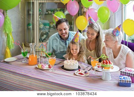 Little girl blows out the candles on the cake