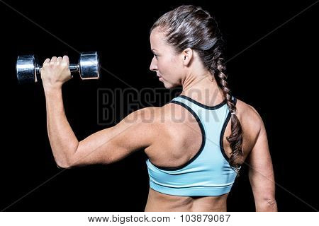 Rear view of woman lifting dumbbell against black background