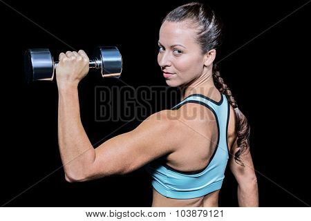 Portrait of woman lifting dumbbell against black background