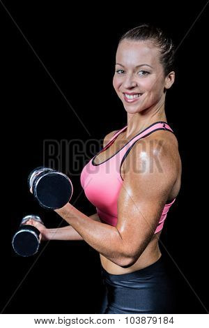 Side view of smiling woman lifting dumbbells against black background