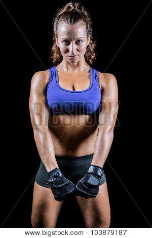 Portrait of confident woman standing against black background