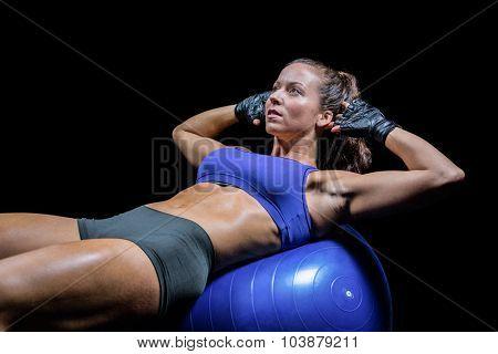 Woman exercising on ball against black bakground