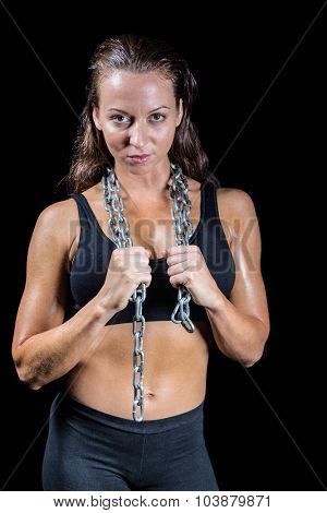 Portrait of confident woman with chain against black background