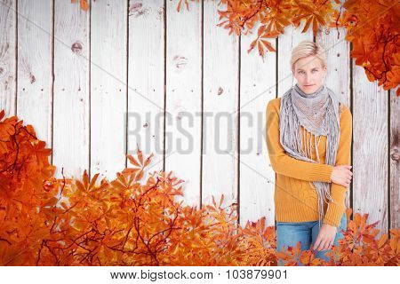 Smiling woman looking at the camera against autumn leaves pattern