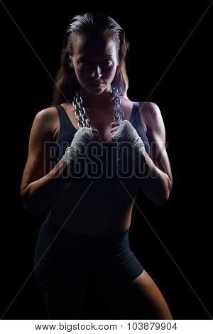 Portrait of female fighter holding chain around neck against black background