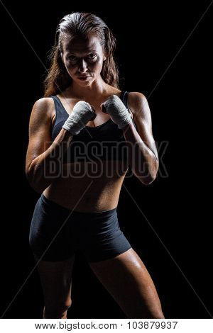 Portrait of female athlete with fighting stance against black background