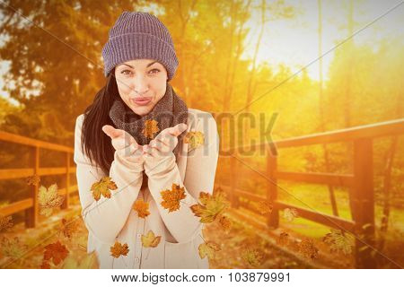 Beautiful brunette smiling at camera and blowing kiss against autumn scene