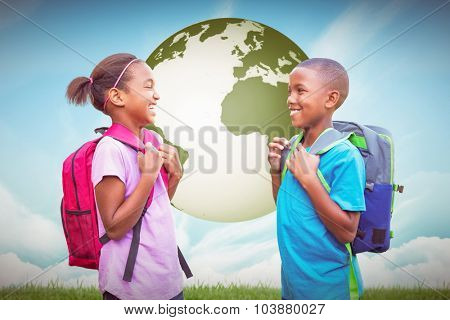 Smiling pupils against blue sky over green field