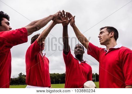 Rugby players putting hands together at the park